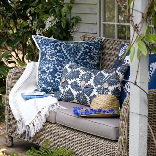 A comfortable wickerwork garden seat with nice blue cushions